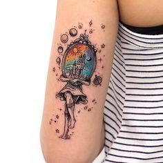 Tatuagem criada por Rob Carvalho de São Paulo.    Menina segurando quadro onde aparece o sol e a noite coloridos.