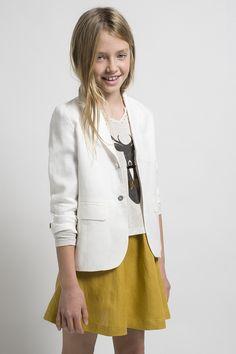 Este conjunto compuesto por una americana blanca y una falda mostaza se convertirá en el look favorito de tu niña.