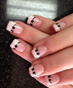 Classic black and white French tips with bows. What makes this extra special is using rhinestones on the bows and outlining the French tip with black polish.