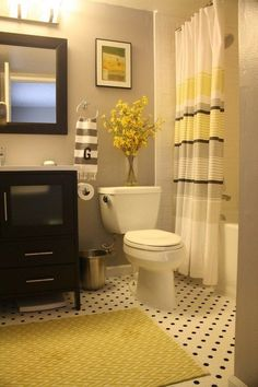 Love this bathrooms color scheme:  black, grey and yellow.  Also. love the vase of flowers.