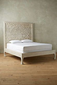 An ornate wooden carved bed fit for a queen.