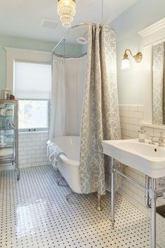 Spa like bathroom features upper walls painted a soothing green and lower walls clad in subway tiles lined with a claw foot tub fitted with a ceiling mounted shower rail and a gray trellis shower curtain next to a Restoration Hardware Pharmacy Small Bath Cabinet Burnished Steel atop a marble basket weave floor.