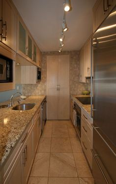 Modern Kitchen with Amber Yellow Granite Countertop, Door Style plymouth, Flat panel cabinets, Undermount Sink, Flush, Galley