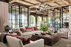 The family room's sofas are upholstered in a Castel cotton from Donghia, and the ottoman/cocktail table is covered in an embossed Bordoni leather from Richard Shapiro/Studiolo; the lounge chairs are by Michael Berman, the chandelier is by Formations, the table lamps are by Gregorius   Pineo, the curtains are made of a Sahco fabric, and the rug is by Tai Ping.