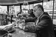 """Man drinking his coffee at the bar of Belcafé in Zurich. On the counter lies a book with the title: """"Bribery and Corruption"""""""