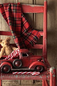 Old toy truck with teddy on red chair