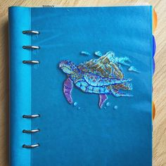 #filofax #clipbook gift for my mother. cover: laminated #illustration of a #turtle mounting the #world. blue and gold gel pens (noname) and white, pink and orange felt tip pens on light blue paper.