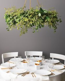 Take a centerpiece to new heights by hanging a ring of flat and glossy camellia leaves horizontally from a beam or hook with gold cord. add viburnum, peruvian apple, and russian olive branches, and vo Hula Hoop Chandelier, Flower Chandelier, Diy Chandelier, Chandeliers, Hanging Centerpiece, Green Centerpieces, Hanging Decorations, Hanging Flower Arrangements, Marquee Decoration