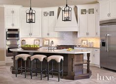 A split-face #backsplash contrasts with the dark island in this #Texas home's #kitchen. See more at www.luxesource.com //Re-pinned by Tara Blais Davison