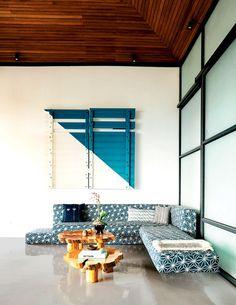 Obra de Dario Escobar acima do sofá em balanço, com estampas geométricas, de Johann Wolfschoon para a Sketch