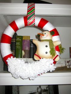 Christmas wreath. Inspired by many websites. Wrap a styrofoam wreath with yarn, add some felt flowers (or in my case, felt snow) and a Christmas ornament and voila!