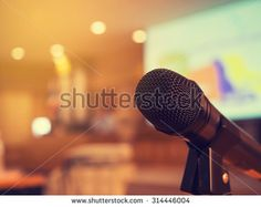 Black microphone in concert hall or conference room with defocused bokeh lights in background. Extremely shallow dof. : Vintage style and filtered process. - stock photo