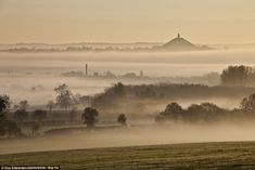 Sure looks like what Bilbo woke up to every morning... Mists and mellow fruitfulness: The hazy hills around Glastonbury Tor in Somerset