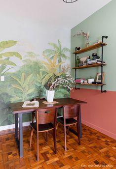 Sala de jantar com painel da Branco. e parede pintada com cores da Suvinil tem estante de ferro e madeira, mesa com cadeiras vintage e piso de taco.
