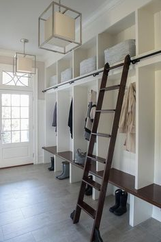 A glass paneled door under a transom window opens to a beautiful white mudroom illuminated by Caged Small Lanterns hung in front of white open mudroom lockers fitted with a dark stained mudroom bench matching a dark stained ladder on wheels, making it easy to reach overhead shelves stuffed with gray baskets. #GlassShelvesLibrary