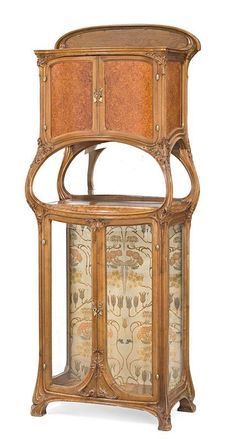 An Art Nouveau walnut and amboyna glazed cabinet, school of Nancy, circa 1905, in the Majorelle style