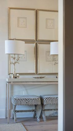 French foyer features a pair of zebra x stools tucked under a gray console table topped with silver leaf branch lamps placed below a collection of framed art.