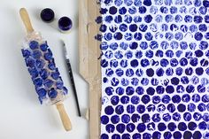 DIY Geschenke mit selbst bedrucktem Stoff verpacken: Luftpolsterfolie mit doppelseitigem Klebeband auf ein Nudelholz kleben, Stofffarbe auftragen und vorsichtig über den Stoff abrollen.