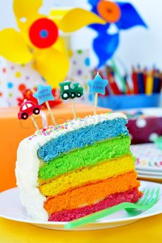 Stock image of 'Slice of a birthday rainbow cake for kids party'
