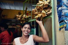 """Woman Selling puso rice at Sinulog Festival in Cebu City, Philippines. Puso rice or """"packed rice"""" is steamed rice cooked and wrapped in palm or coconut leaves. The leaves give a peculiar flavour to the rice, which is usually accompanied to other dishes or enjoyed as healthy on-the-go meal."""