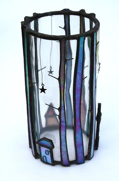 Tall trees and little houses surround these decorative candle holders. Designed to be placed over a tea light they shine in a dark corner and reflect the light in the day. The iridescent glass creates a magical finish and looks beautiful all day long! Candle Jars measure approximately 17cm high and 8.5cm in diameter. The height can vary within 1-2 cm) This listing is for the Winter Forest Candle Jar *Actual item will vary from those pictured. Glass types/colours used are the same however…