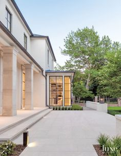 Stocker's contemporary take on classic Georgian architecture includes a colonnade composed of columns with pared-down capitals and a façade in white-painted brick. Most of the rooms receive light from multiple exposures. Britt Johnson of Britton & Associates handled the landscape installation and was a collaborator throughout the landscape design and plant selection process.