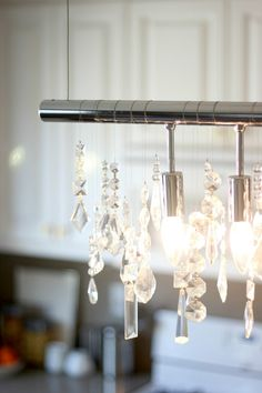 The linear design in our exquisite Linear Strand Crystal Chandelier deflects the light of nine bulbs through numerous shapes and sizes of faceted crystals. The crystals can be re-arranged simply by shifting them along the aluminum rod.Photo via The Glitter Guide.