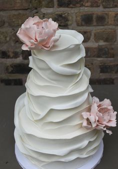 Elegant layer texture white wedding cake topped with pink flowers; Featured Cake: Alliance Bakery