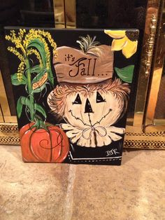 Painted fall canvas with scarecrow and pumpkin.
