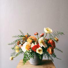 orange ranunculus, poppies, and white peonies