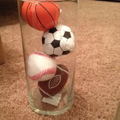Cylinder vases with sports balls for a sports themes baby shower. You can find the variety of balls at party city