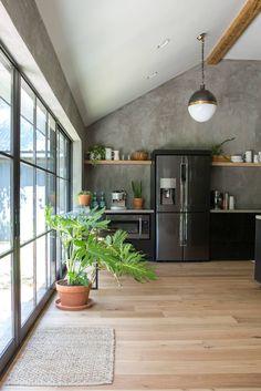 Beautiful fridge, and hidden microwave below countertops. The Pick A Door House - Magnolia Market