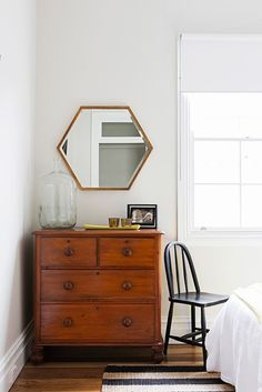 "Cassie and Tim's bright Inner West semi:A black-painted chair and polygon mirror in bronze from [Project 82](http://www.project82.com.au/?utm_campaign=supplier/|target=""_blank"") contrast with the antique chest of drawers."