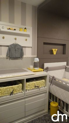 Decoração de quarto de bebê em tons de cinza, amarelo e branco. Utilizamos papel de parede listrado,o enxoval da cama babá e berço foram personalizados. Quadrinhos com as mesmas cores foram produzidos em mdf com a imagem dos minions super heróis.