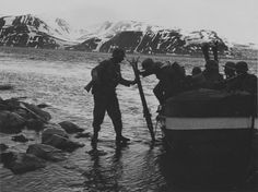 """Soldiers of 6. SS-Gebirgs-Division """"Nord"""" disembarking their boat on the Arctic shore in 1941."""