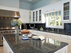 Oversized Kitchen Island with White Cabinetry and Blue Walls - on HGTV