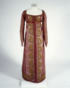 Red gauze dress with chenille embroidery. A light open weave fabric woven in Scotland, gauze or leno. The dress shows signs of having been cut down from an adult garment to fit a child.     Date  1808 AD - 1808 AD     Image Number  002106  Museum of London