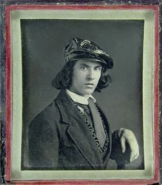 Handsome young man with long hair and wearing a cap