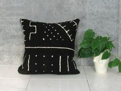 Black and White Mudcloth Pillow Cover  This pillow cover is made with an authentic mudcloth textile, or bogolanfini, hand-made by artisans in Mali, Africa. It is hand spun on a loom with natural, unprocessed cotton and then colored and designed with all natural dyes and fermented mud. This complicated process dates back to the 12th century. This particular piece of mudcloth is a true black with a white print. The back of the pillow is made with a cream colored natural linen. It has an…