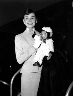 The actress Audrey Hepburn (holding a toy monkey) photographed during her arrival at the Los Angeles International Airport in Los Angeles, California (USA), from Paris (France), on February 27, 1956.Audrey was wearing:Suit: Givenchy (of flannel in a shade of apricot, blazer single-breasted with buttons of resin in the same color, and skirt in a straight line, both pieces lined with silk, of his collection for the Spring/Summer of 1955).Scarf: Givenchy (of white silk with black polka dots, of…
