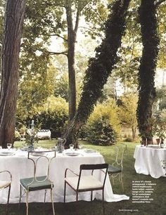 Lovely outdoor tea party.  Long white table linens, mix of vintage metal chairs and lush natural gardens.