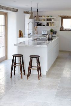 Blenheim Grey Brushed Limestone floor by Mandarin Stone. White kitchen, but tempered by touches of wood for a rustic feel.