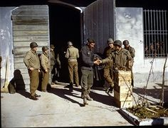 At an Anzio beachhead POW Holding Center, a German prisoner of war (a Luftwaffe soldier, possibly a paratrooper) (center, in blue) is issued C Rations by a US Army private, Anzio, Italy, early 1944. Other German POWs watch from the barred window at right. C Rations consisted of two cans, one (the M Unit) contained a meat and vegetable and the other (the B Unit) contained bread (usually crackers), desert, a powdered beverage, and condiments. Pin by Paolo Marzioli