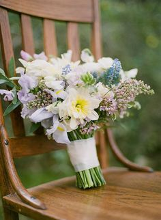 A purple and blue bouquet by @mayhar with daffodils, lilacs, sweet peas, and muscari | Brides.com