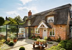 A glassed-in modern kitchen addition adds elegance to a thatched-roof cottage in England without sacrificing the home's quaint European style.