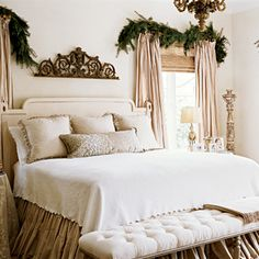 The master bedroom, with worn finishes of antique architectural elements, exudes a rustic elegance. Swags of pine bring notes of Christmas into the bedroom.