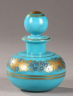 Small perfume bottle in blue turquoise opaline with its ball shaped cork. A wreath of roses, anemones and forget-me in gold and dark blue is surounded by golden stripes...