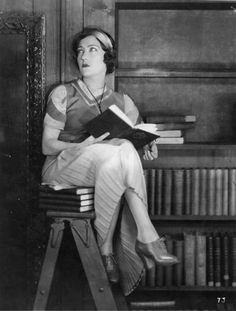 Gloria Swanson reading on library ladder (c. 1920).