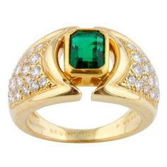 This Boucheron 18k gold ring features a translucent Colombian emerald of exceptional quality and color. There are 38 round brilliant diamonds approx. 1.10 cts. Emerald is approx. 1 ct. Circa 1980s