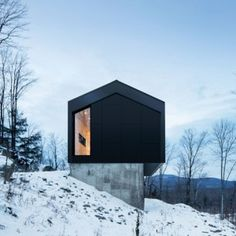 Quebec+residence+by+Naturehumaine+is++raised+off+a+slope+on+a+concrete+podium
